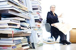 woman in office surrounded by books and papers